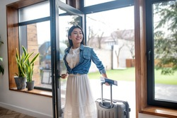 Travel plans. Dark-haired female opening glass door, pulling her suitcase, entering the house
