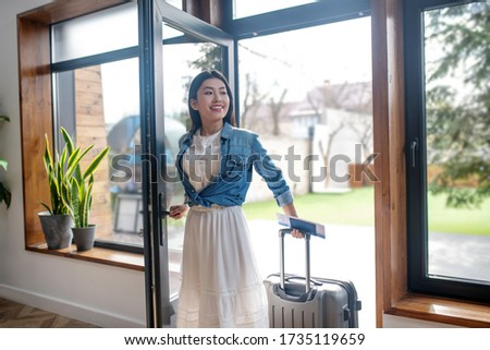 Travel plans. Dark-haired female opening glass door, pulling her suitcase, entering the house Zdjęcia stock ©