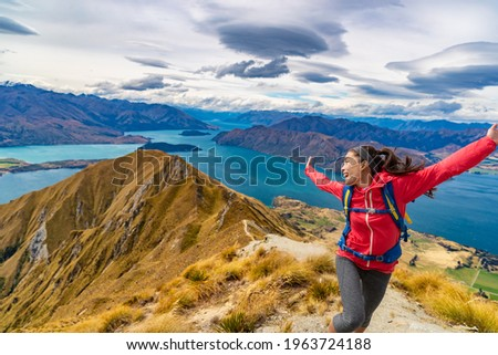 Travel post Covid-19 concept. Pent-up traveling demand concept. Hiker jumping of joy funny - woman hiking in New Zealand laughing having fun, joyful and aspirational at Roys Peak, South Island. Foto stock ©
