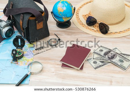 Travel preparation : compass, money, passport, road map ,hat,sunglasses,magnifying glass on wooden table #530876266