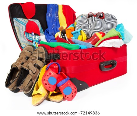 Travel red suitcase. Packed for vacation in sea resort. Family personal belongings: slippers, sandals, hat, towel. Isolated on white