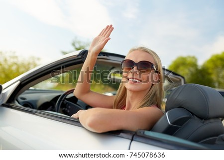 travel, road trip and people concept - happy young woman in convertible car waving hand #745078636