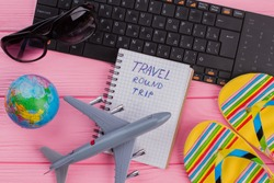 Travel round trip on notebook with woman's traveler accessories glasses wallet and flip-flops on pink table top background. Globe black keyboard grey airplane.
