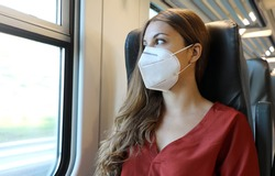 Travel safely on public transport. Young woman with face mask looking through train window. Train passenger with protective mask traveling early morning to go to work.