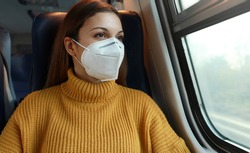 Travel safely. Young business woman with KN95 FFP2 face mask looking through train window. Train passenger with protective mask travels sitting in business class looking through the window.