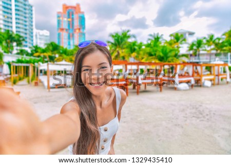 Travel selfie Asian tourist woman on vacation on South Beach resort hotel in Miami, Florida, USA holiday. Luxury vacations getaway. #1329435410