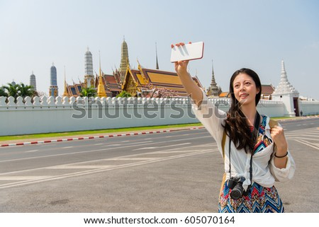 Travel selfie smart phone by woman in Bangkok Thailand, Asia. Happy smiling Chinese Asian girl taking self portrait photo sitting on street by the grand palace of holiday concept.