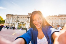 Travel selfie vlogger live streaming video online asian tourist woman social media influencer taking photo at Buckingham Palace London, UK. Europe summer vacation people lifestyle.