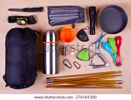 Travel set. Tourist outfit for camping or hiking. Various professional tools and items for outdoors pastime on beige background. #276569300