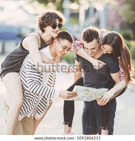 Travel, sightseeing, vacation, holidays, adventure, friendship, togetherness. Group of young people planning vacation looking at touristic map #1091806211