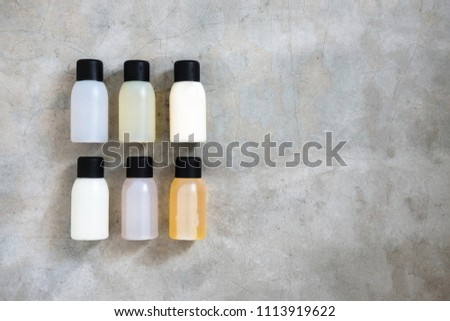 Travel-sized mini bottles cosmetic products from above on concrete table. Skincare, moisturizers, essences, body and hair treatments. Minimalism blogging concept.