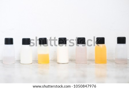 Travel-sized mini bottles cosmetic products. Skincare, moisturizers, essences, body and hair treatments. Minimalism blogging concept.