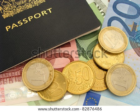 Travel spending - Close up of Euro coins and bills surrounding a passport