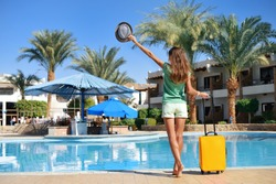 Travel, summer holidays and vacation concept - Beautiful woman faceless walking near hotel pool area with yellow suitcase in Egypt