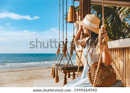 Travel summer vacation concept, Happy traveler asian woman with hat and dress relax on swing in beach cafe, Koh Chang, Thailand