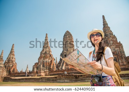 Travel Thailand Ayutthaya tourist woman on Asia sightseeing holding map with big pagoda and spectacular buddhist attraction in Wat Chaiwatthanaram. Tourism people concept with mixed race Asian girl. #624409031