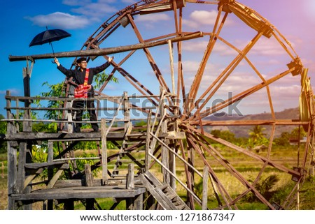 Travel Thailand concept, tourist wearing Thai dam clothes and standing on water windmill  to farm and traveling in Thai dam village in Thailand