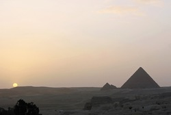 Travel to Egypt, a dust storm in the desert, sunset over the one of seven wonder of the world, the great ancient pyramids, twilight.