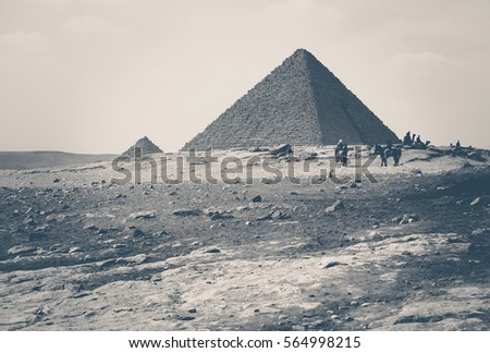 Travel to Egypt in retro style - typical landscape with great egyptian pyramids and silhouettes of tourists. Monochromatic photo of ancient pyramid on Giza Plateau in Cairo.