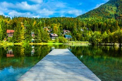 Travel to fabulous Slovenia. Lake Jasna in the Eastern Julian Alps. Wooden pier. The mountains are overgrown with dense mixed forest. On the banks there are lovely houses with red roofs.