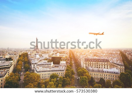 travel to France, airplane flying over beautiful panoramic cityscape of Paris with Eiffel Tower