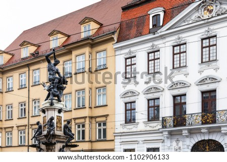 Travel to Germany - Hercules statue on Herkulesbrunnen fountain near rococo Schaezlerpalais palace on Maximilianstrasse street in Augsburg city in rainy spring day