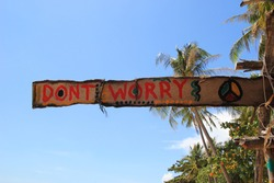 Travel to island Koh Lanta, Thailand. An inscription (Don't worry) on the wooden abandoned hut on a sky background.