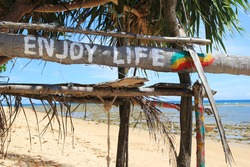 Travel to island Koh Lanta, Thailand. An inscription (Enjoy life) on the wooden abandoned hut on a beach background.