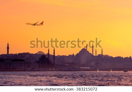 Travel to Istanbul on passenger transport in Turkey. Sunrise in golden colors with soft light effect. Turkish landmarks - panoramic cityscape of Istanbul with silhouette of mosques on seaside.