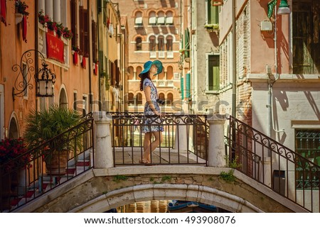 Travel to Italy. Young woman in summer dress and blue hat with camera posing on the bridge in Venice. Venice is popular tourist place in Europe.