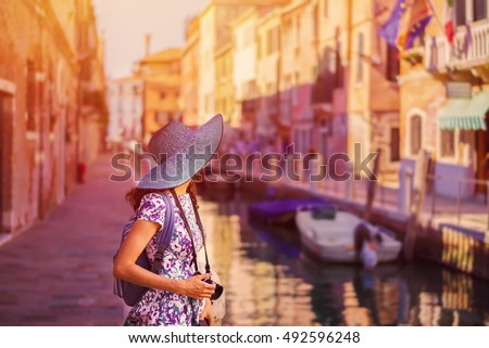 Travel to Italy. Young woman in summer dress and blue hat with camera posing on the medieval street in Venice. Venice is popular tourist place in Europe.