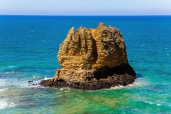 Travel to the Southern Hemisphere.  Pacific coast and sandy beach. Fabulous journey to Australia. Alumina residues - cliffs  in the snow-white foam of the ocean surf.