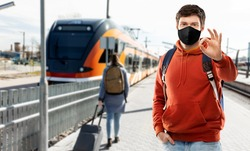 travel, tourism and pandemic concept - young man with backpack in face protective medical mask showing ok hand sign traveling by train over railway station in city of tallinn, estonia on background