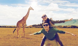 travel, tourism and people concept - happy couple with backpacks having fun over giraffe in african savannah background