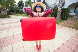 Travel, tourism and people concept- happy girl in hat carry a big red suitcase and smiling