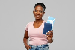 travel, tourism and vacation concept - happy young african american woman with air ticket and passport over grey background