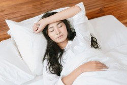 travel tourism concept of Asian beautiful woman resting in bed at hotel room yawning falling sleeping comfortably relaxing feeling sick having nightmare on holiday vacation accommodation taking break