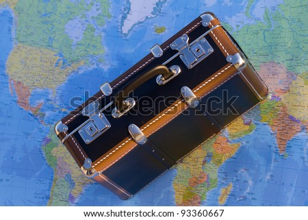 Travel, tourism - old suitcase on blurred world map in background