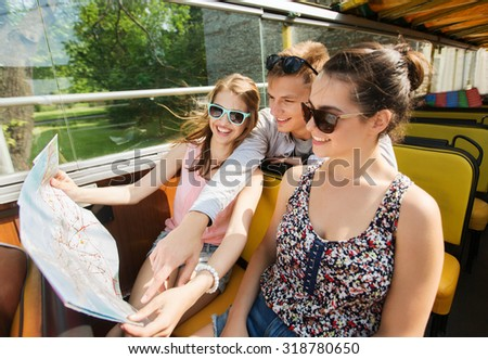 travel, tourism, summer vacation, sightseeing and people concept - group of smiling teenage friends in sunglasses with map traveling by tour bus