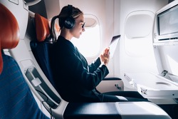 Travel tourism with modern technology and air flights concept, Caucasian woman sitting in plane with modern digital gadget and searching favourite music playlist in application for listening
