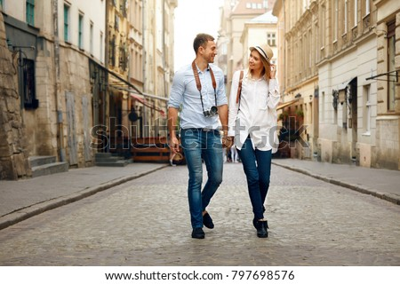 Travel. Tourist Couple Traveling, Walking On Street. Portrait Of Beautiful Young Woman And Handsome Man In Stylish Clothes Sightseeing City Attractions, Looking At Architecture. High Resolution.