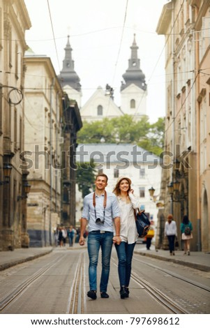 Travel. Tourist Couple Traveling, Walking On Street. Portrait Of Beautiful Young Woman And Handsome Man In Stylish Clothes Sightseeing City Attractions, Looking At Architecture. High Resolution. #797698612