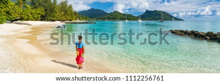 Travel tourist woman at French Polynesia beach on Huahine island cruise excursion on Tahiti holiday vacaton. Girl wearing polynesian sarong skirt banner panorama crop.