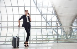 Travel tourist woman standing with luggage check flight number on smartphone airport. Young business girl with her suitcase waiting at boarding gate before departure. Travel lifestyle concept