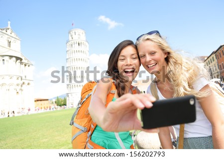Travel tourists friends laughing taking photo with smartphone. Women girlfriends traveling in Europe smiling joyful having fun taking self-portrait picture in Pisa by Leaning Tower of Pisa, Italy.