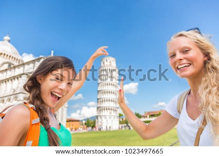 Travel tourists friends selfie at Pisa having fun posing for picture. Two girls backpacking on Europe summer vacation taking photo at popular attraction with funny pose.