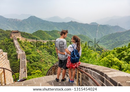 Travel tourists people sightseeing in China travel vacation. Happy interracial couple enjoying Great wall of China landscape near Beijing city. Asia travel summer holidays together.