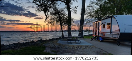 Travel trailer camping at sunset by the Mississippi river in Illinois at sunset panorama