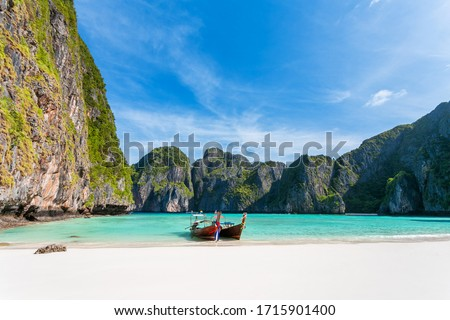 Travel tropical beach, background Summer beach, of Maya Bay, with a longtail boat, parked overlooking white sand beach, clear water, and beautiful sky, Phi Phi Leh island, Krabi Province, Thailand.