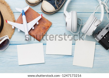 Travel vacation background concept with sun hat, camera, passport, airplane toy, headphones and photo frames on wooden backdrop. Top view with copy space. Flat lay